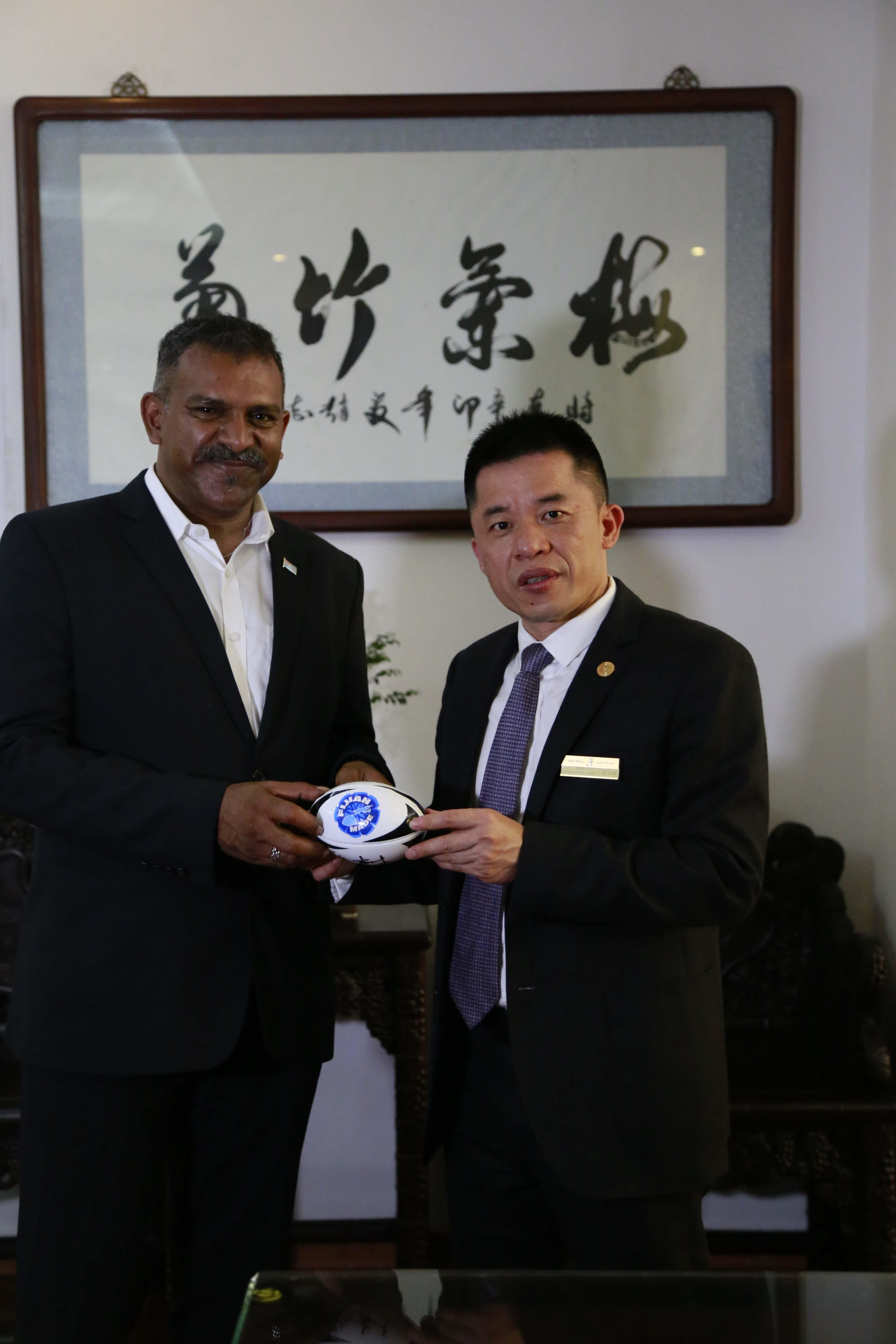 法亚兹·科亚先生和陈玉树先生共同在橄榄球上签名共证友谊天长地久